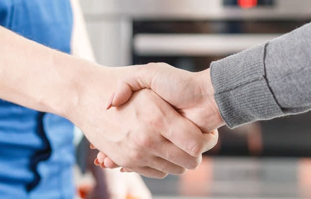 Close-up of expert and customer shaking hands after repairing the fault