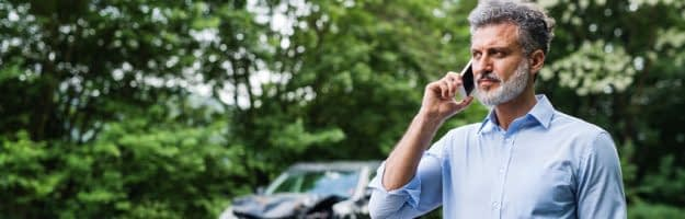 Handsome mature man making a phone call after a car accident