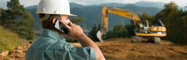 Male engineer talking on the phone while supervising construction. Case and Project Management. Technical Assistance.